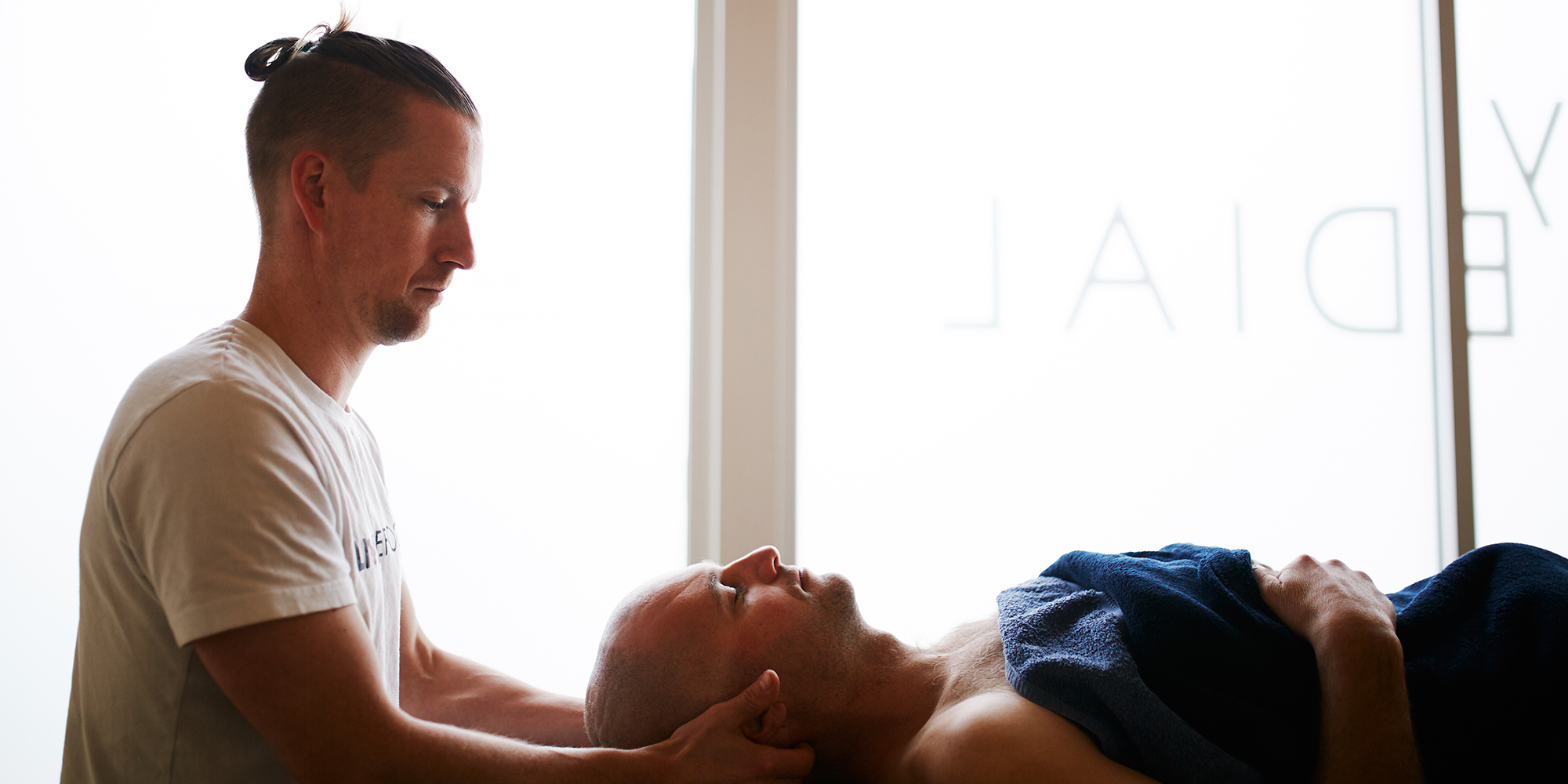 therapist holding client's head in their hands while performing neck massage